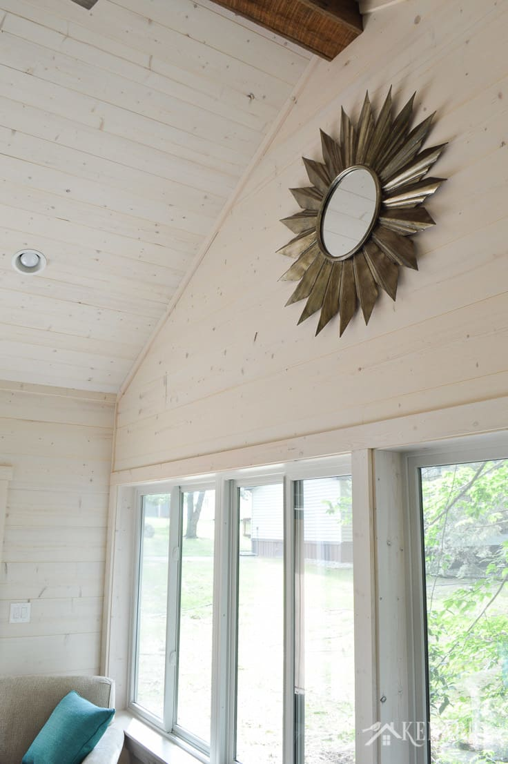 A vaulted ceiling with shiplap walls and a large metal sunburst mirror add industrial style to a sunroom in a cottage | shiplap walls | plank wall | whitewashed pine wood walls | home decor | home ideas | farmhouse style
