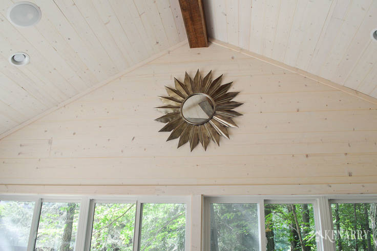 A large metal sunburst mirror adds industrial style to this cottage sunroom with vaulted shiplap ceiling and walls | shiplap walls | plank wall | whitewashed pine wood walls | home decor | home ideas | farmhouse style