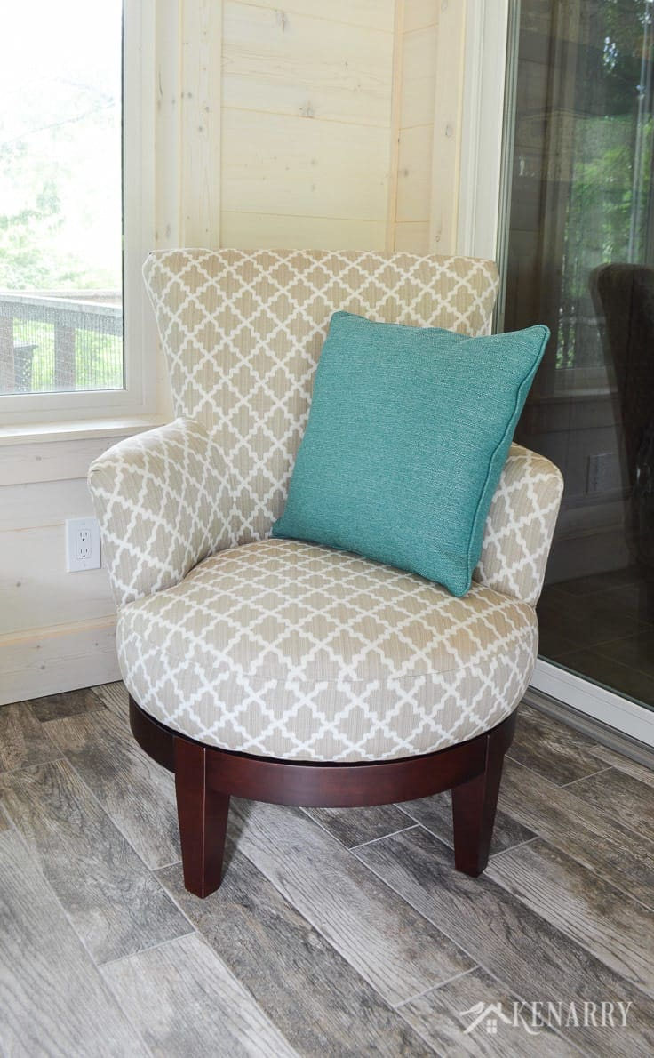 Justine side chair from Best Home Furnishings in Silver 28843 with a DePalma Ocean turquoise or teal throw pillow from England Furniture | cottage sunroom | glass sliding door | footstool | hinged ottoman with storage | rattan lamp with side table | shiplap walls | plank wall | whitewashed pine wood walls | porcelain tile floor | wood tile flooring | home decor | furniture | home ideas | farmhouse style