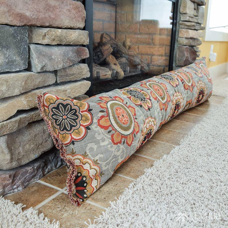 Turn an old body pillow into a fireplace draft stopper. This easy sewing tutorial is perfect for beginners. Plus a DIY draft blocker will help to save heating costs and block cold air this winter. draft stopper | draft protector | draft excluder | door draft blocker