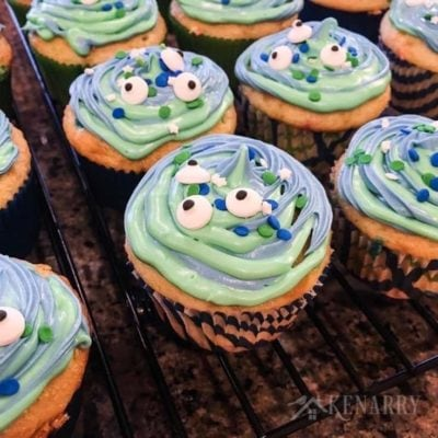 Blue and green swirl frosting with festive sprinkles and candy eyes make cute alien or monster cupcakes for a birthday party or Halloween treat.