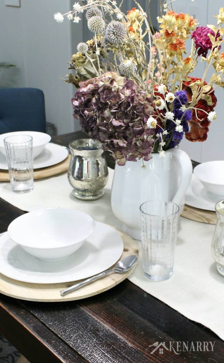 Fill a large white pitcher with fresh or dried flowers as an eye catching centerpiece that adds a wow factor to your Thanksgiving table decor. Pair it with timeless white dishes on wood chargers for stylish yet simple holiday entertaining.