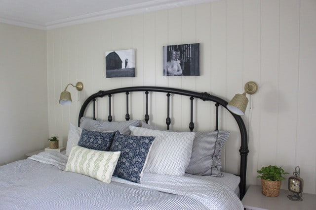 A bed with a brass headboard and 2 lamps on the wall