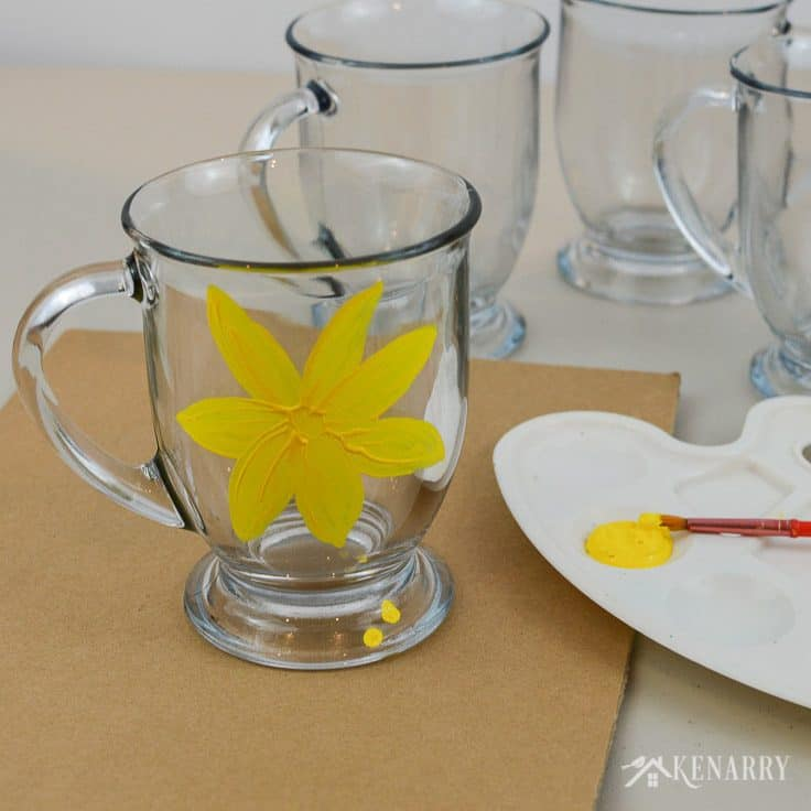 Use yellow gloss enamel craft paint to create a floral design on DIY coffee mugs. What a fun and easy craft idea!
