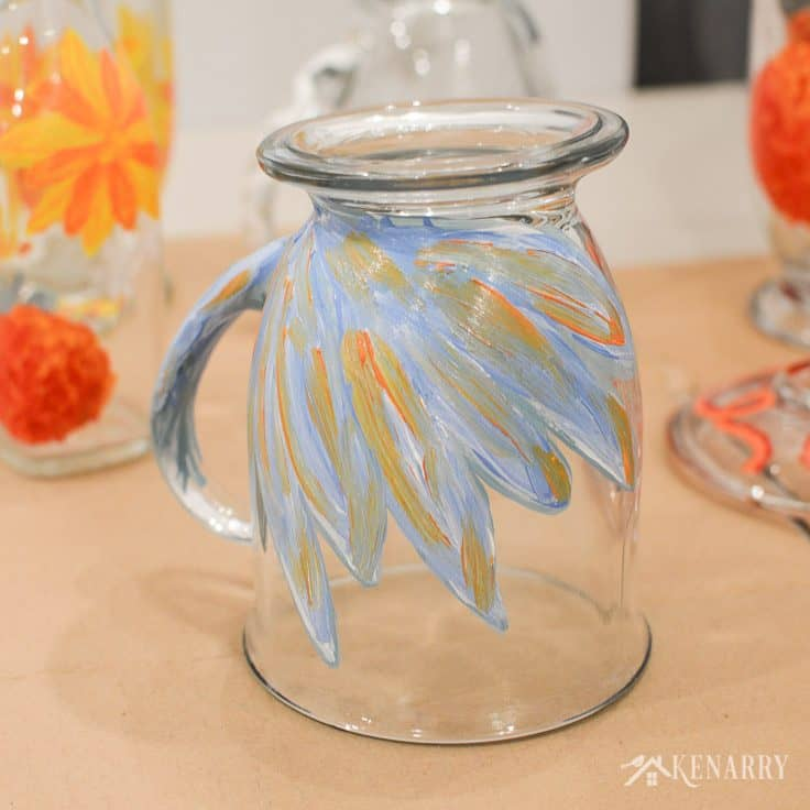 Blue, orange, and white gloss enamel paint mix together to create a beautiful flower design on DIY coffee mugs.