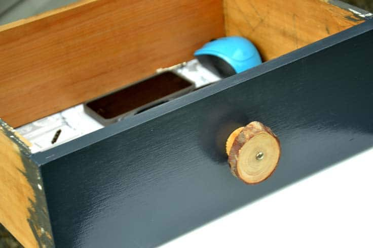 picture of navy blue drawer front with a wood slice drawer pull