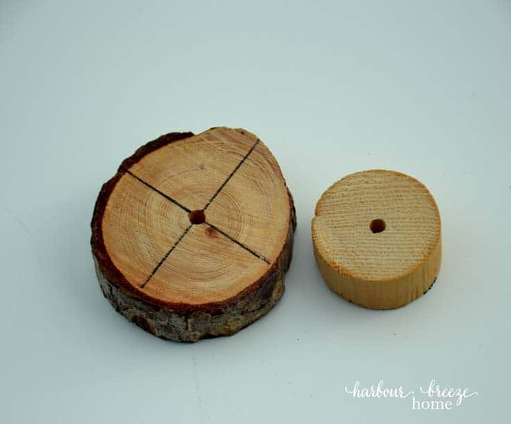 a wood slice from a branch with and a wooden dowel with holes drilled in the center of each