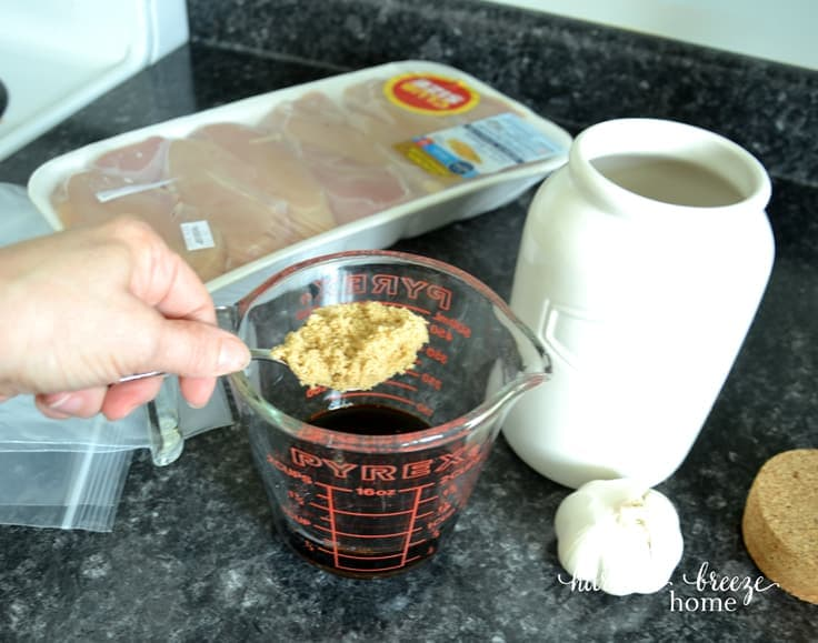 a spoon full of brown sugar being poured into a measuring cup of soy sauce