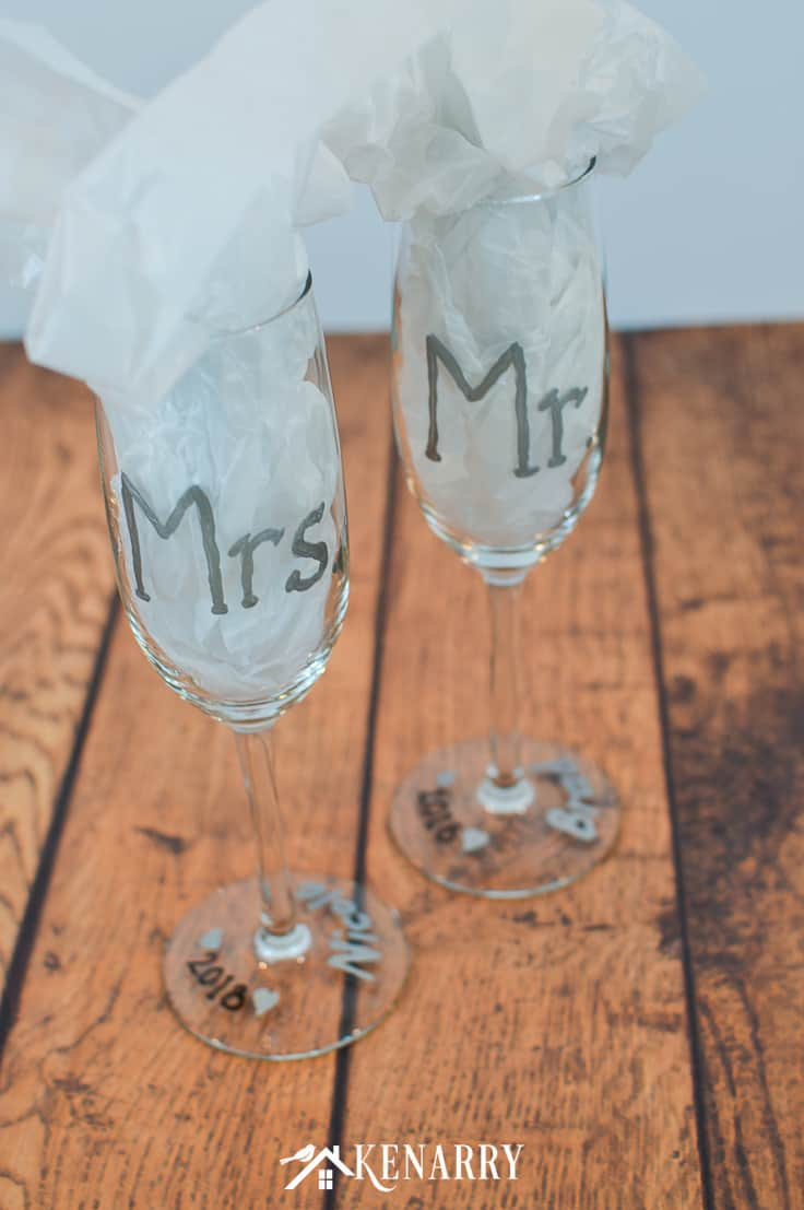 Mr. and Mrs. toasting glasses are an easy DIY gift for the bride and groom. Use gloss enamel paints to personalize hand painted champagne flutes. These champagne glasses are perfect for a bridal shower, wedding or anniversary. #weddinggifts #weddingideas #giftideas #handpainted