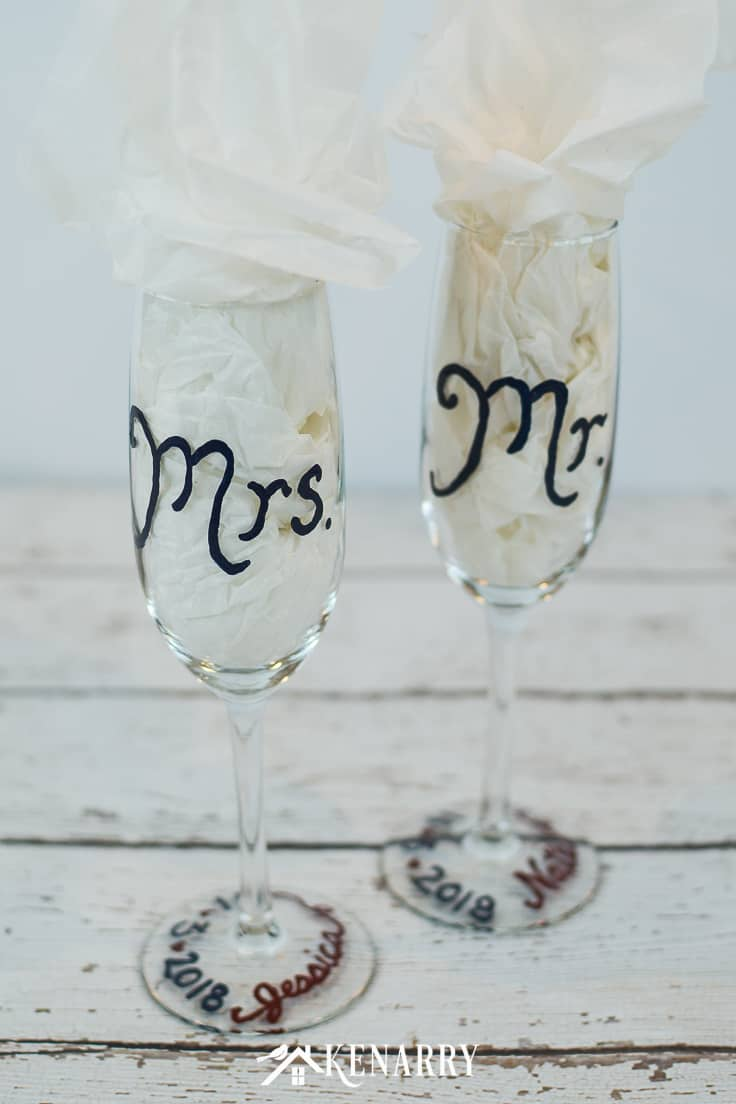 Customize champagne flutes with gloss enamel paints. These Mr. and Mrs. toasting glasses are an easy DIY present. Wedding glasses for the bride and groom are perfect for a bridal shower gift. #weddinggifts #weddingideas #diygift #handpainted