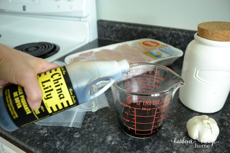 soy sauce being poured into measuring cup