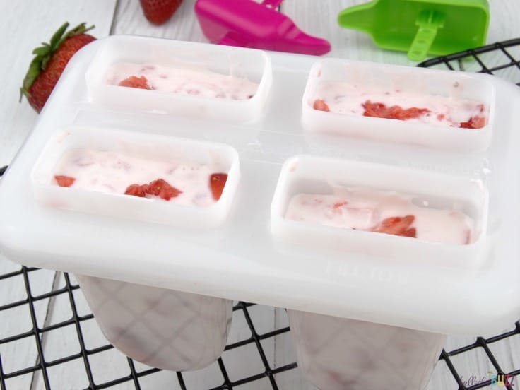 Strawberry Vanilla Yogurt Popsicles fill popsicle molds