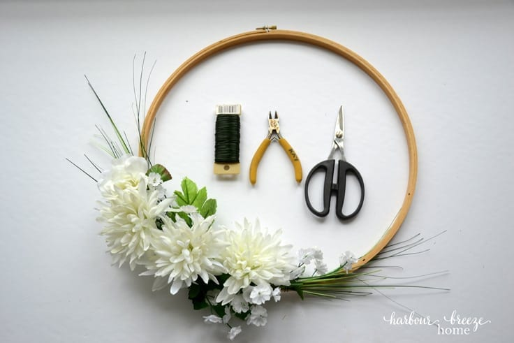 Add small flowers and greenery to fill in an arrangement on an embroidery hoop wreath