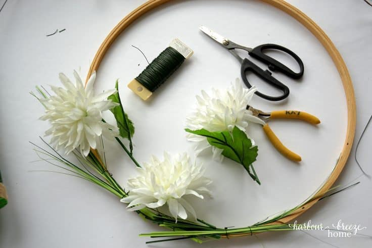 Attach flowers one at a time to an embroidery hoop wreath