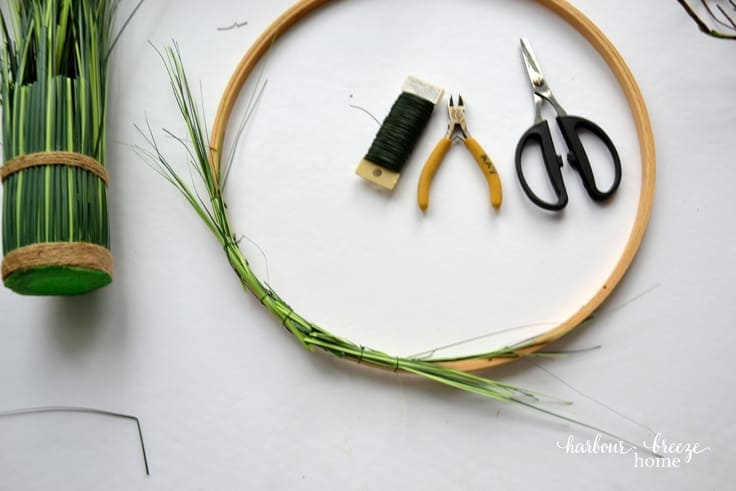 wired on greenery on an embroidery hoop wreath