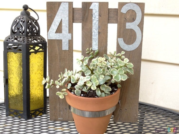 House address sign with a hanging planter