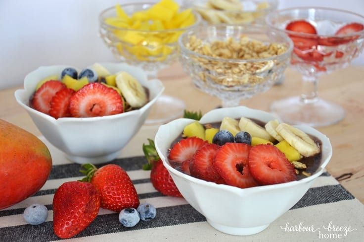 Front view of açaí berry bowls topped with fresh fruit and granola