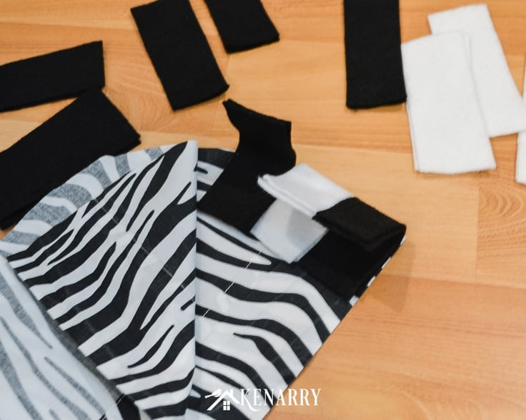 Black and white felt and zebra striped fabric make up this easy zebra costume to make for a child to wear for Halloween or every day dress up.