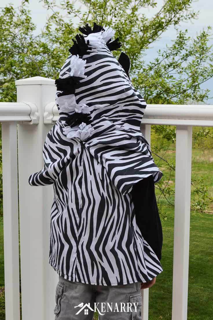 The back of this kids zebra costume shows the fluffy mane made with black and white felt. Learn how to create this zebra costume for a child to wear as a cute Halloween idea or for dress-up clothes. #diyhalloweencostume #halloween #costume #halloween #kidscostumes #diycostumes #kenarry