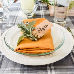 photo of thanksgiving table setting with mustard yellow napkin and fresh herbs