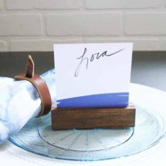 A wood place card holder with a simple blue and white place card. Add a shibori napkin with leather napkin ring for a modern place setting. Image by Craftivity Designs