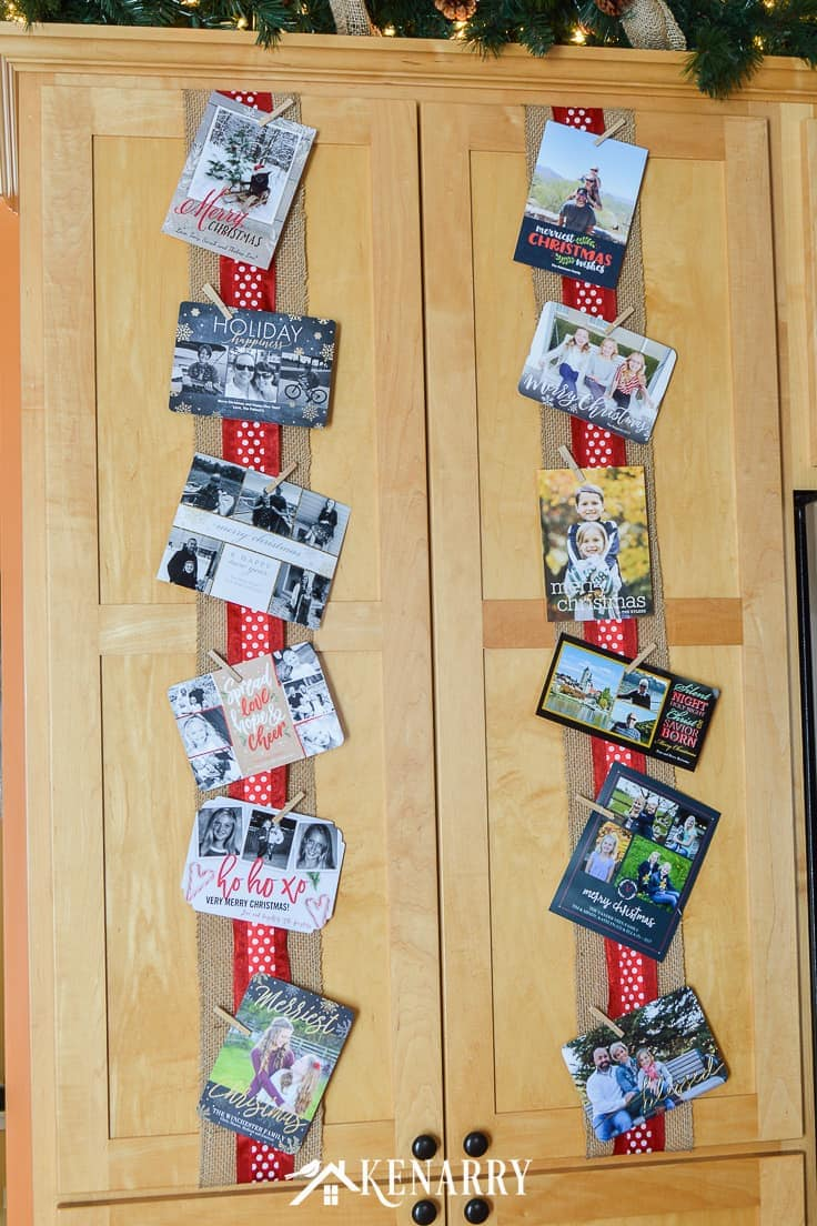Use wide ribbon, burlap and small clothes pins for displaying Christmas cards on your kitchen cabinets so you can enjoy looking at them throughout the holidays. #christmascards #christmas #kenarry