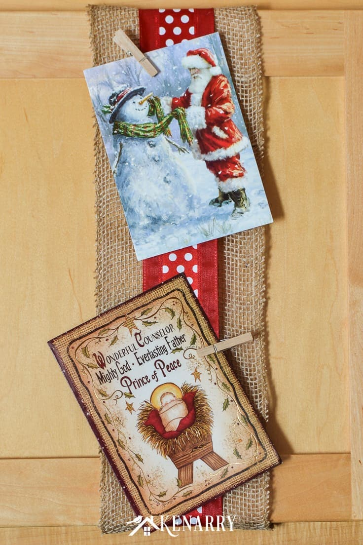 Use wide ribbon, burlap and small clothes pins for displaying Christmas cards on your kitchen cabinets so you can enjoy looking at them throughout the holidays. It's a super easy DIY idea to display your cards for the season! #christmascards #christmas #kenarry