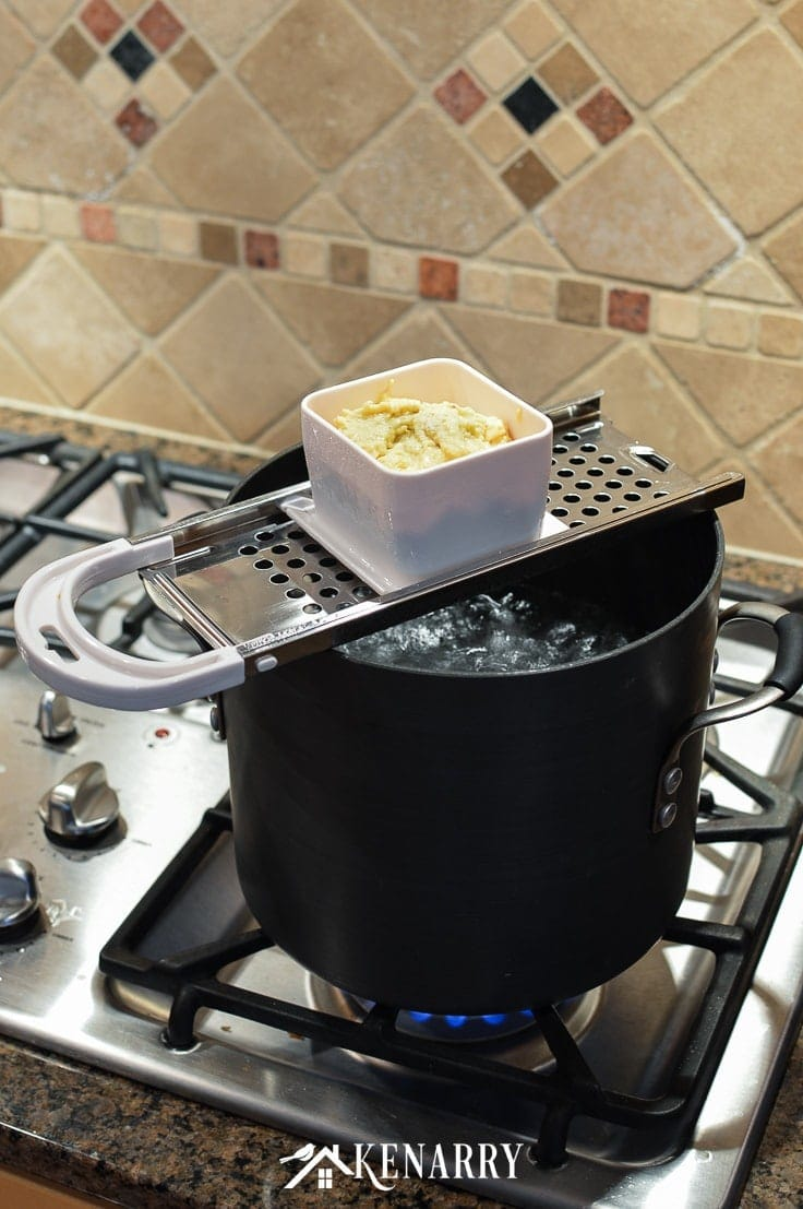 a pot of boiling water on a stove with a spaetzle maker and noodle dough