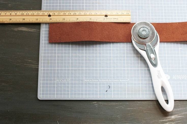 Cut the leather for a personalized leather keychain with a rotary cutter.