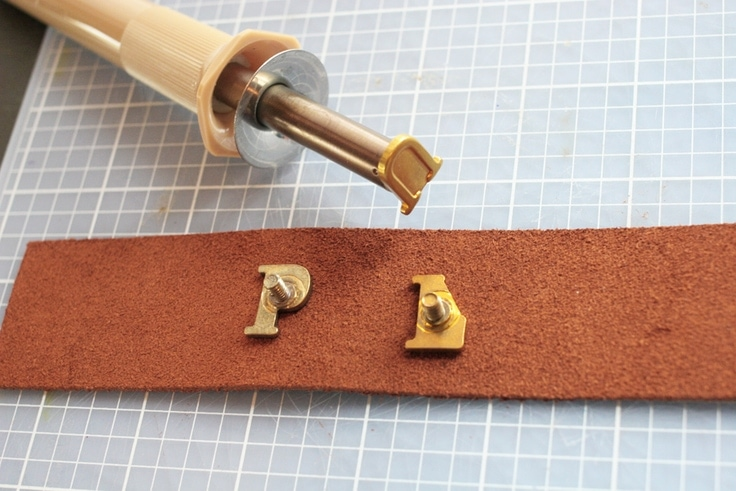 Burn the leather for a personalized leather keychain with a woodburning tool and alphabet hot stamps.