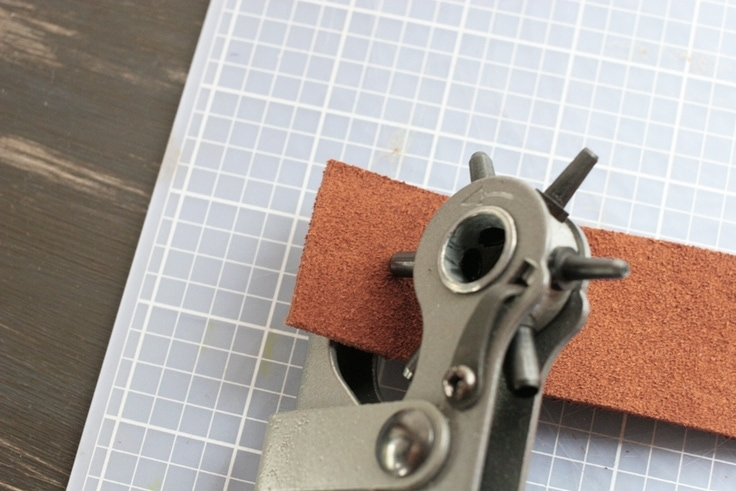 Punch a hole in the leather for a personalized leather keychain with a leather hole punch.