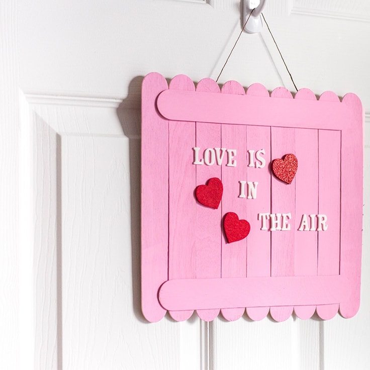 Show 'em that you care with this super easy DIY Valentine's Day wall sign. It's a beautiful Valenine's craft for kids and adults. C'mon! It's time to spruce-up your home for the most romantic time of the year! #valentines #valentinecrafts #kenarry