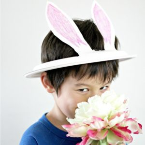 A boy smiling wearing a paper plate bunny hat