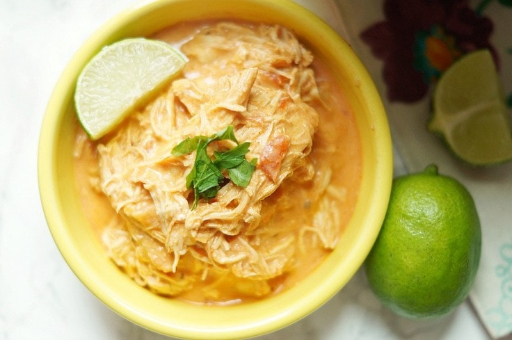 Shredded chicken in a  yellow bowl with a slice of lime on top.