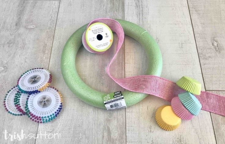 Supplies needed to make a spring wreath out of cupcake liners: Foam wreath, ribbon, cupcake liners, and straight pins.