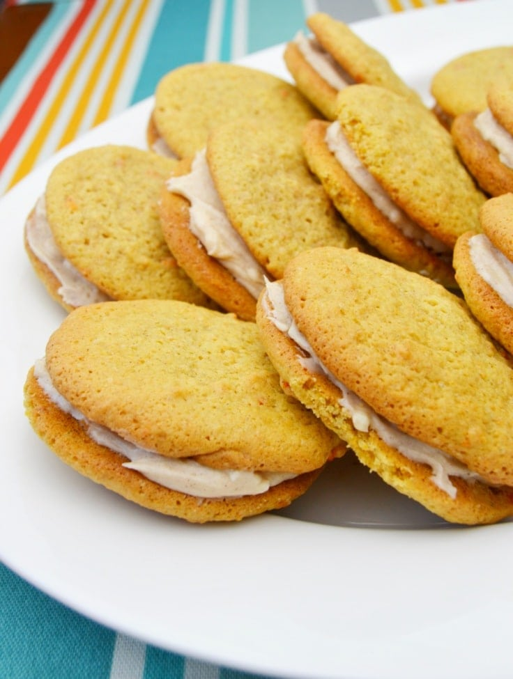 carrot cake cookie sandwiches with cinnamon cream cheese frosting on a plate