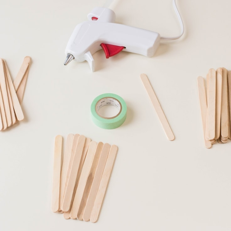 An overhead image of popsicle sticks, green washi tape and a glue gun.