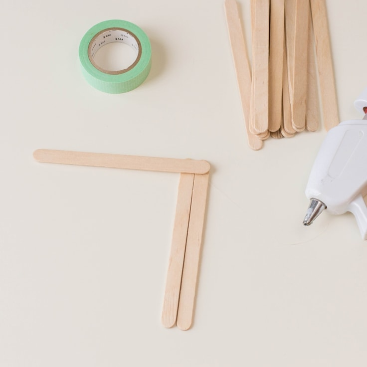 How to make a popsicle stick craft - second step is to glue another stick horizontally on top of the other two sticks.
