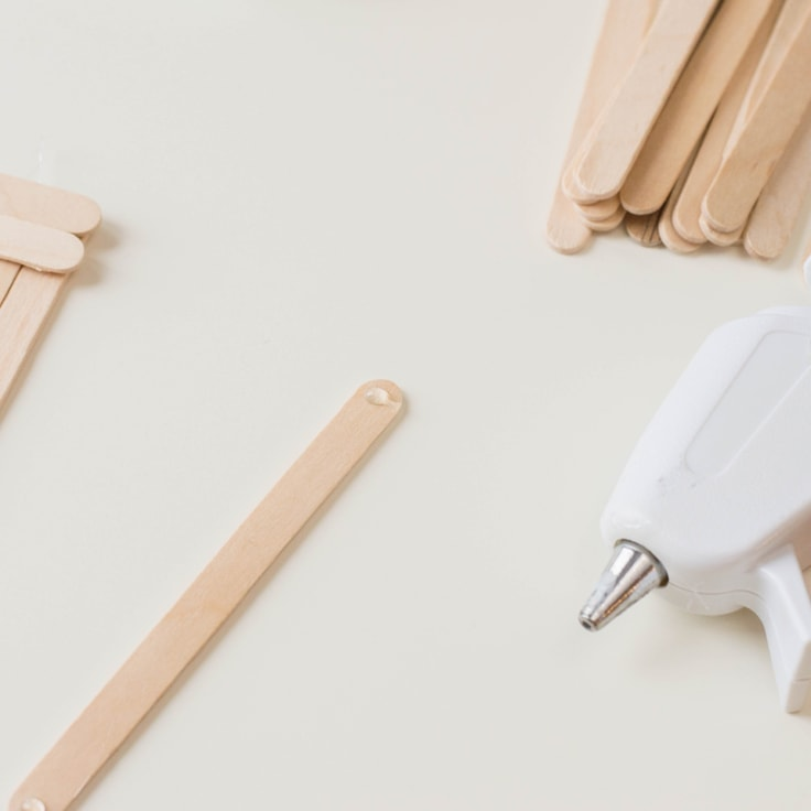 How to make a popsicle stick craft. Fourth step is to put a dap of hot glue on the end of a stick.