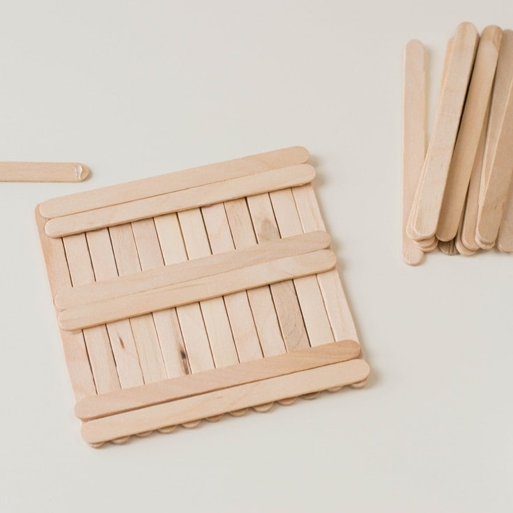 How to make a popsicle stick craft. Fifth step is to flip the coaster over upside down and create a base of perpendicular sticks glued on.