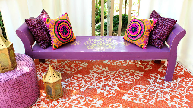 A boho bench , painted purple wtih orange and pink pillows