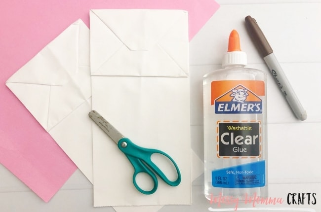 To make an Easter Bunny Bag Puppet you just need paper bags, scissors, clear glue, and a black marker.