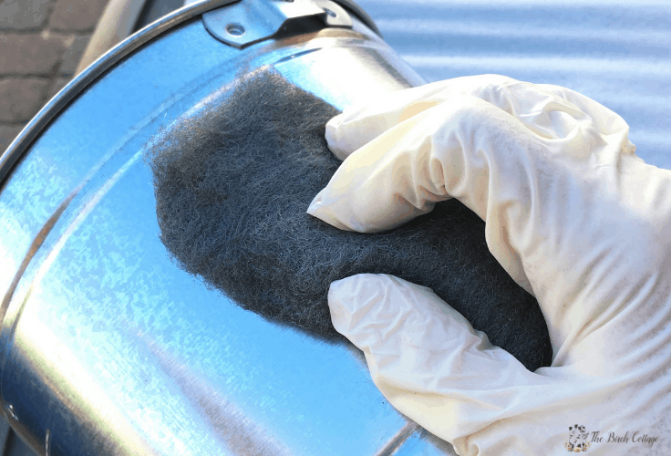 Using steel wool on a metal pail.