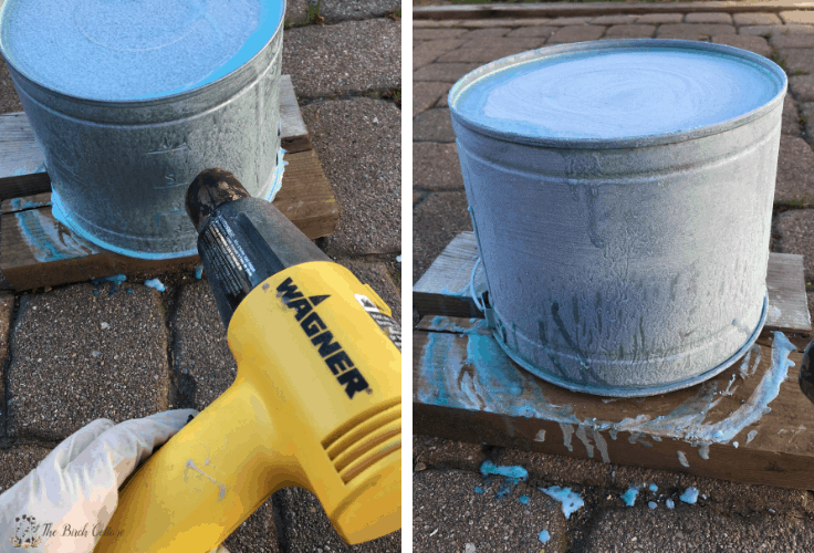 Using a heat gun to age a galvanized metal pail.