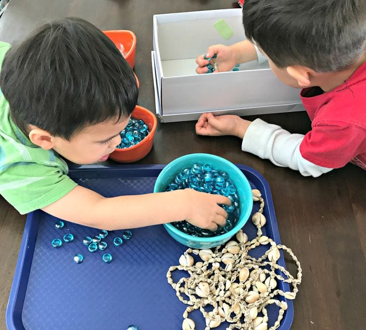 Small boys sort glass gems and seashells into different bowls.