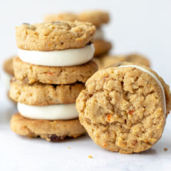 An oatmeal raisin carrot cookies is standing vertically on end so you can see the chunks of minced shredded carrot. Next to it on the left there are two carrot cake cookies stacked on top of one another. Each cookie is actually cream cheese frosting layered between two oatmeal raisin cookies like a cookie sandwich.
