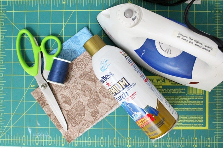 scissors, iron, fabric, thread, and starch on a craft table