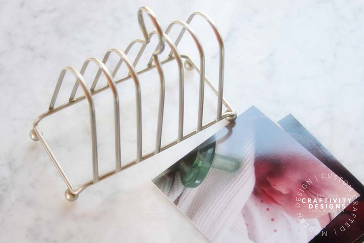 Photos on a marble countertop next to a gold file holder.