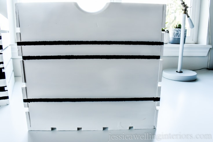 A white wood crate with black horizontal lines painted on it.