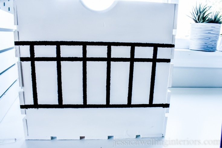 Black painted lines both horizontal and vertical to make boxes on the white wood storage crate.